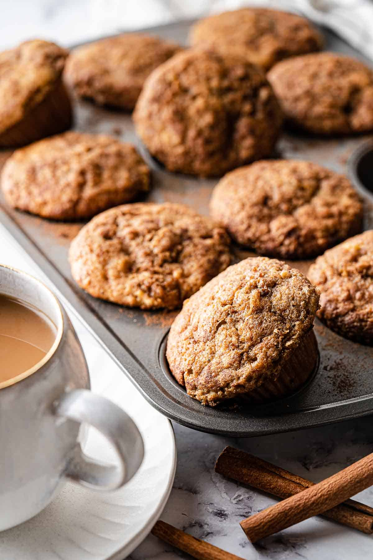 brown butter apple muffins in tin with coffee on the side