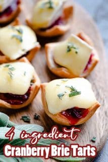 cranberry brie tarts on wooden board with sage on the side and text overlay