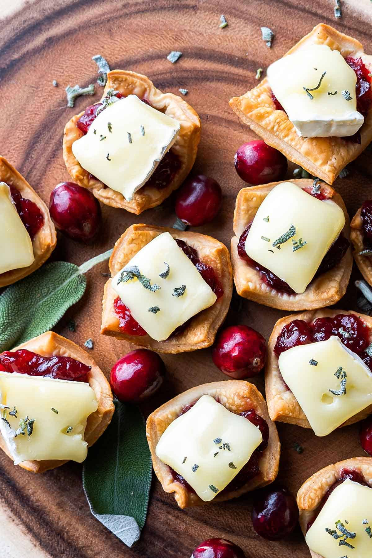 Cranberry Brie Tarts on wooden tray with sage