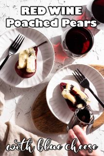 poached pears and blue cheese on two plates with red wine syrup being poured on top