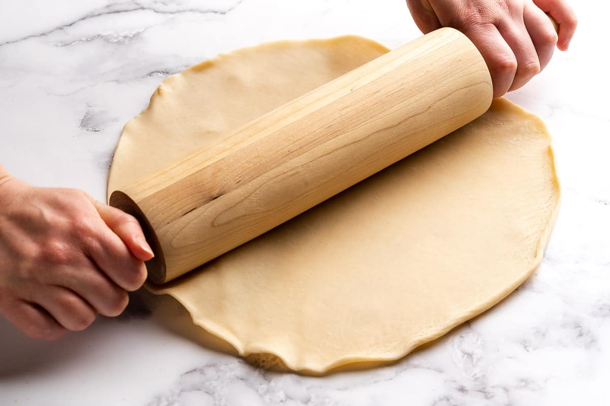 Pie dough being rolled out with wooden rolling pin