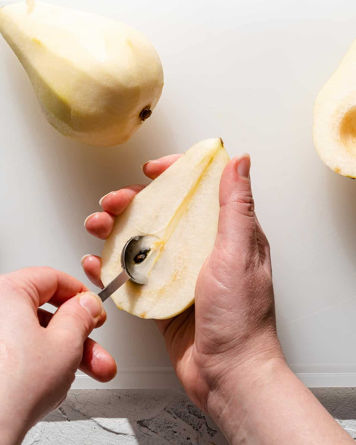 teaspoon scooping seeds out of peeled pear