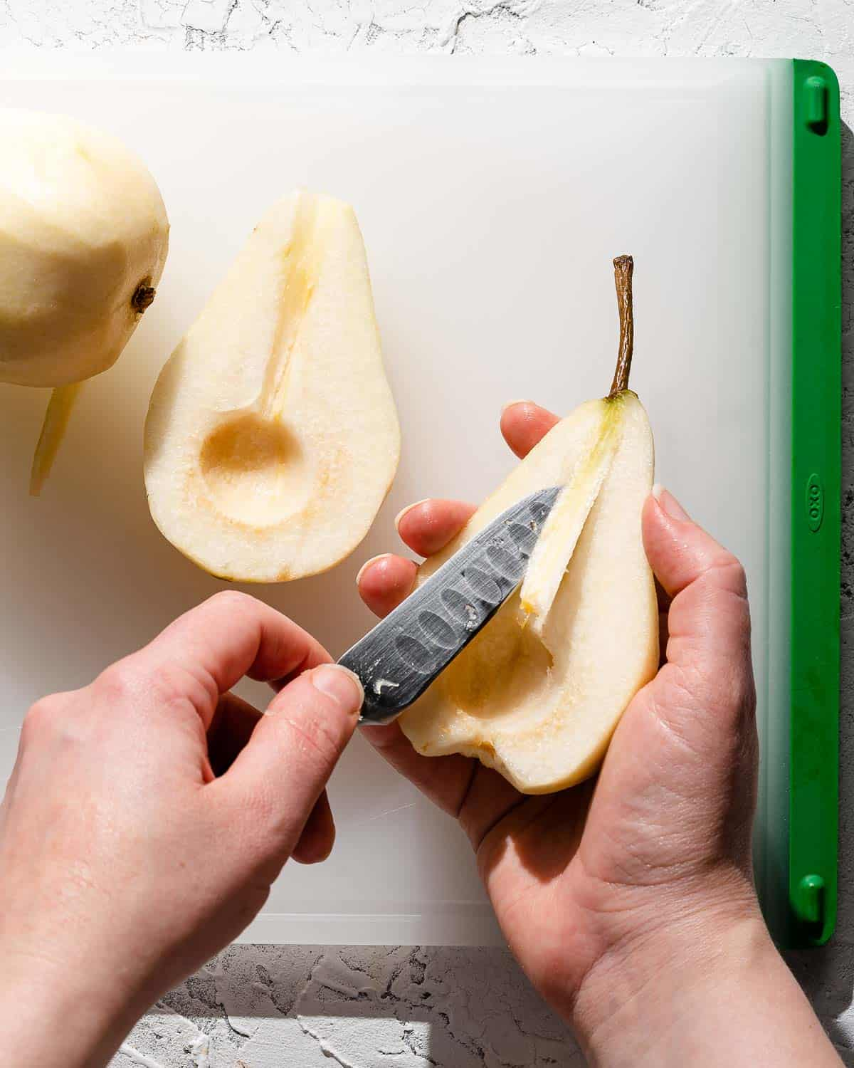 paring knife cutting stem out of center of pear