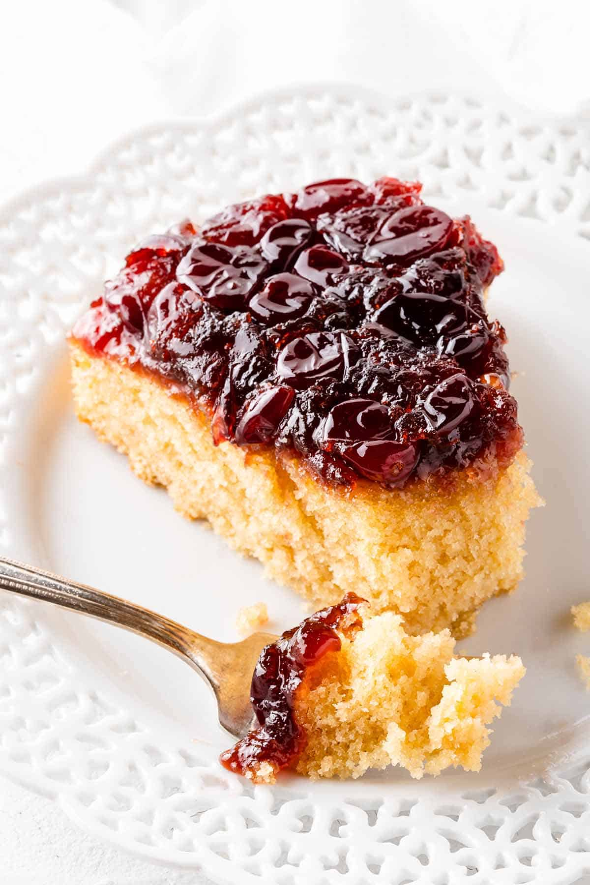 Slice of Cranberry Upside Down Cake with fork on white plate