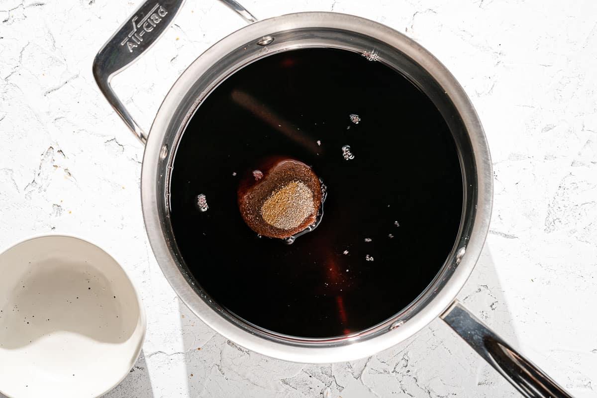 cinnamon stick, sugar and wine in saucepan