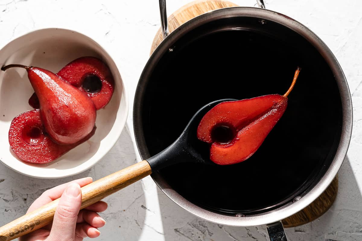 Poached pear being removed from wine with slotted spoon