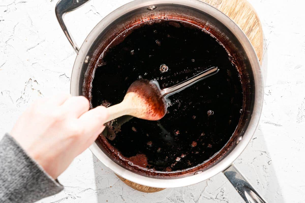 Spoon dragging through red wine syrup in saucepan