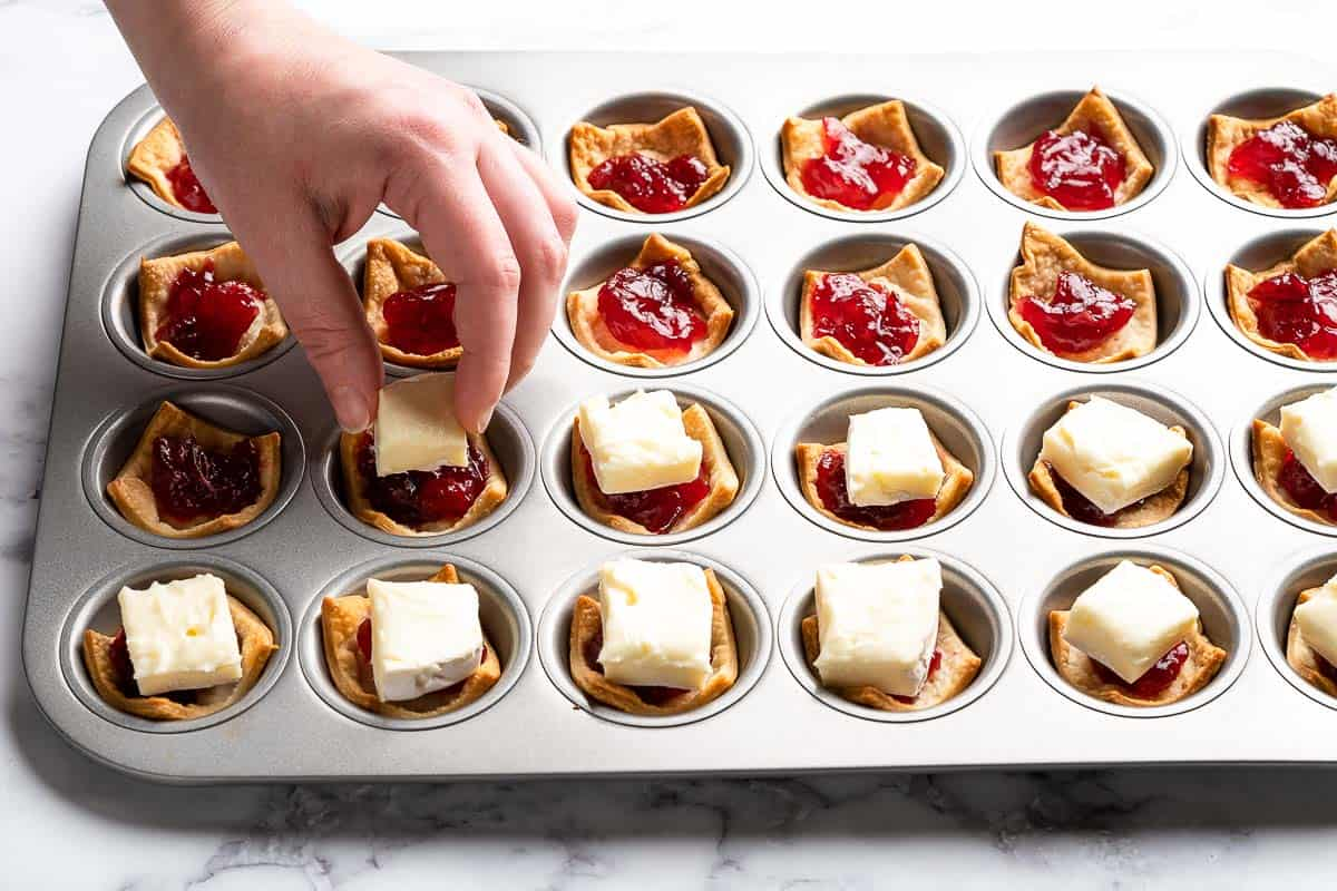 hand adding squares of brie on top of cranberry sauce in tart shells