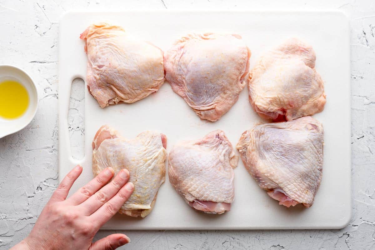hand rubbing oil on chicken thighs