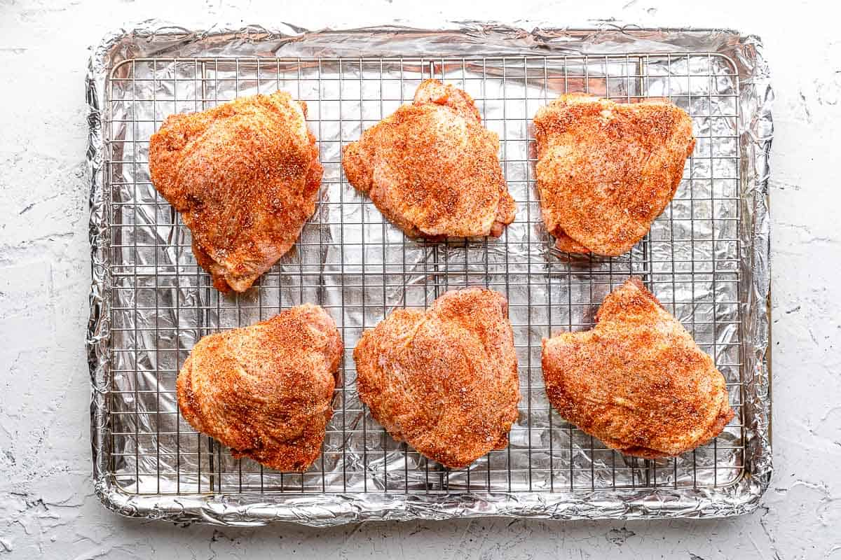 seasoned chicken thighs on wire rack on baking sheet