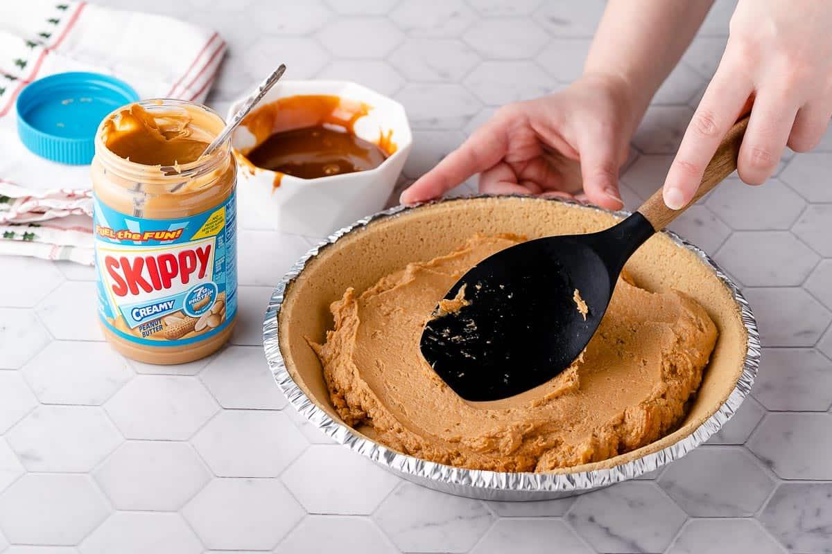 Spreading peanut butter filling inside pie crust