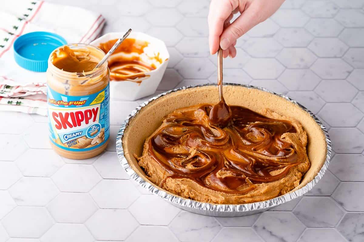Spoon swirling caramel into peanut butter filling in pie