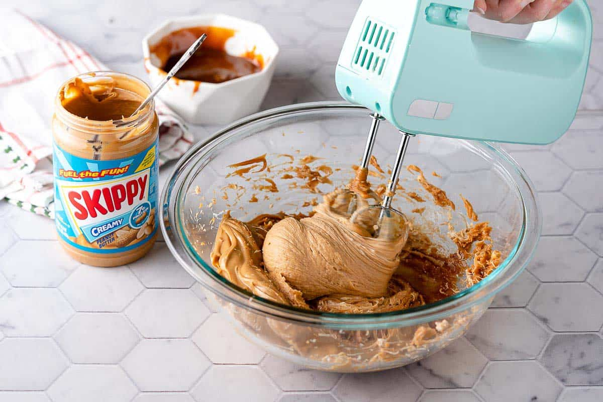 Hand beaters whipping peanut butter filling in glass bowl