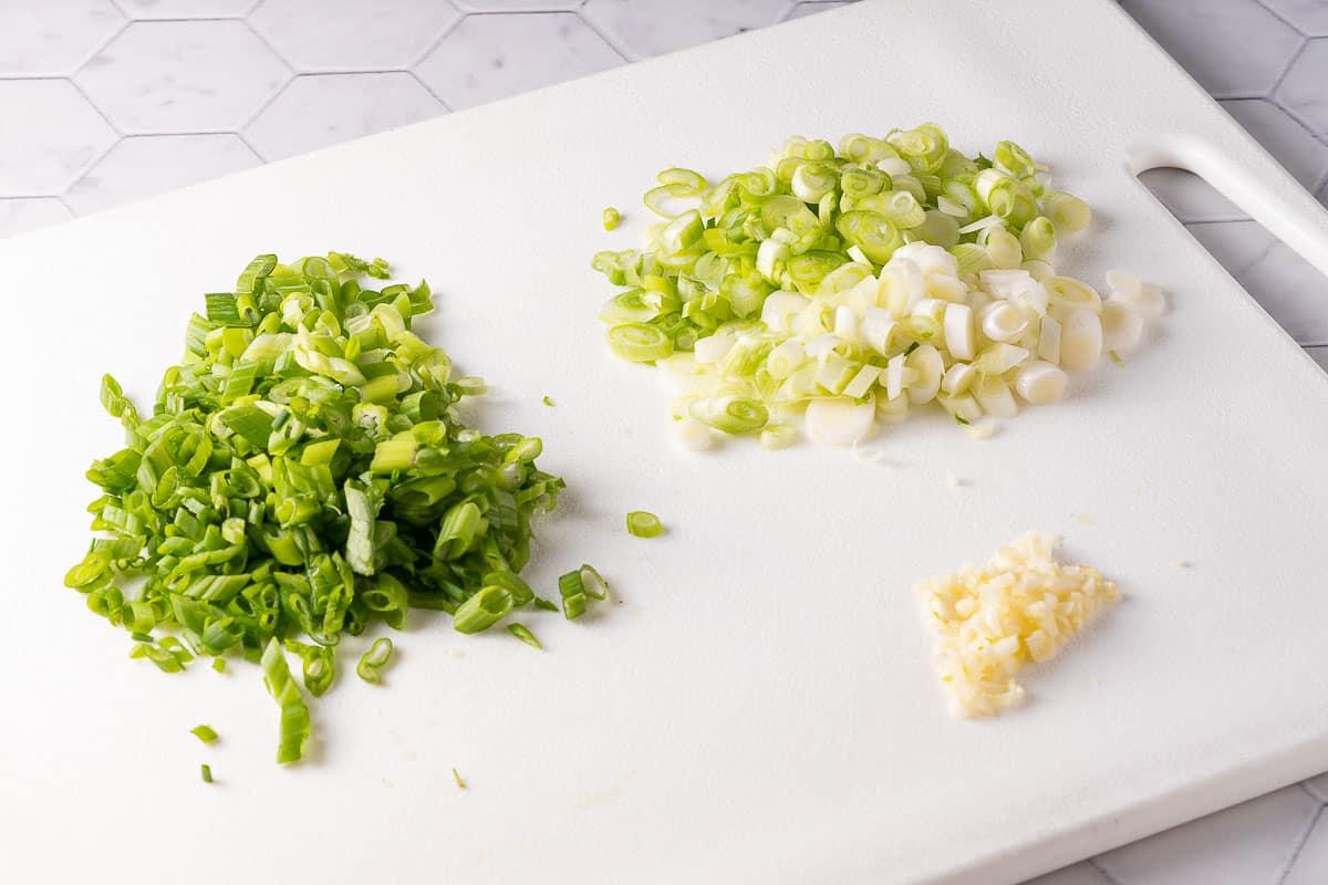 chopped green onion and garlic on cutting board