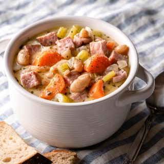 ham and white bean chowder in white bowl with bread