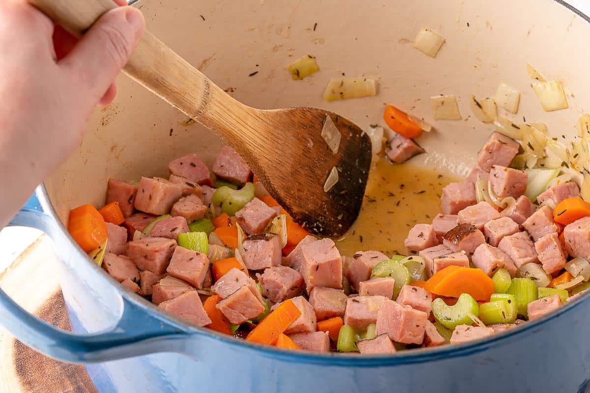 spoon stirring ham and veggies in stock pot