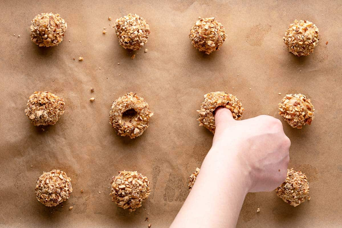 thumb pressing into center of cookie dough ball
