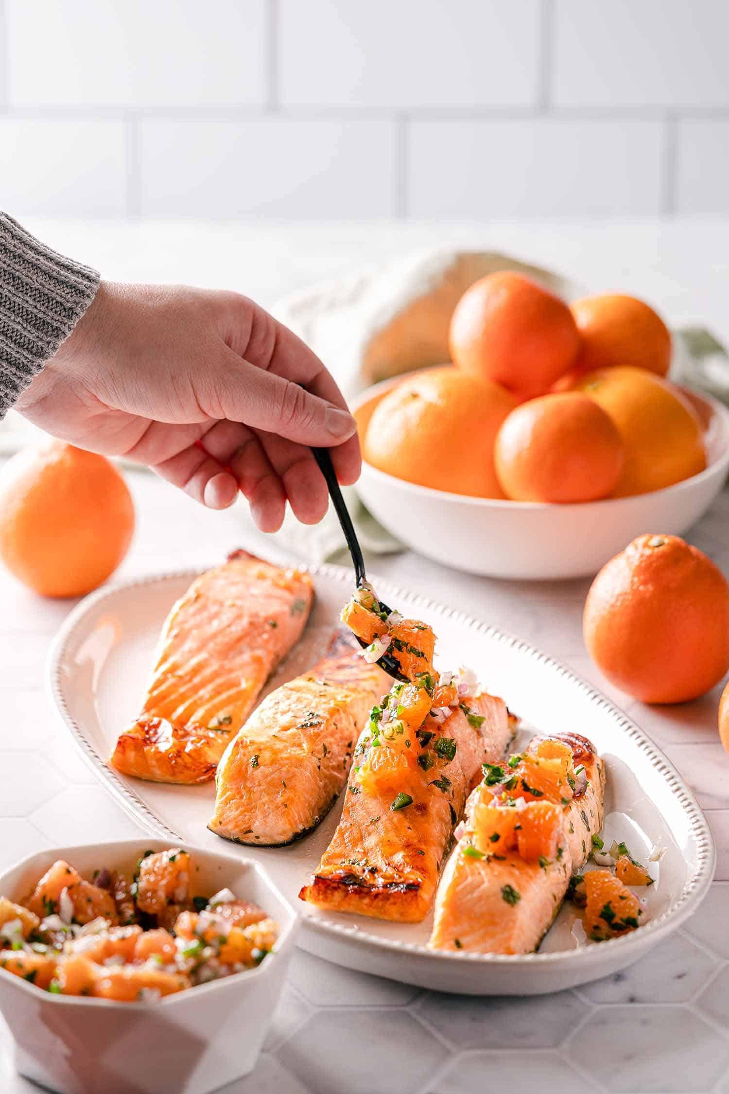 hand spooning orange salsa over broiled salmon on platter