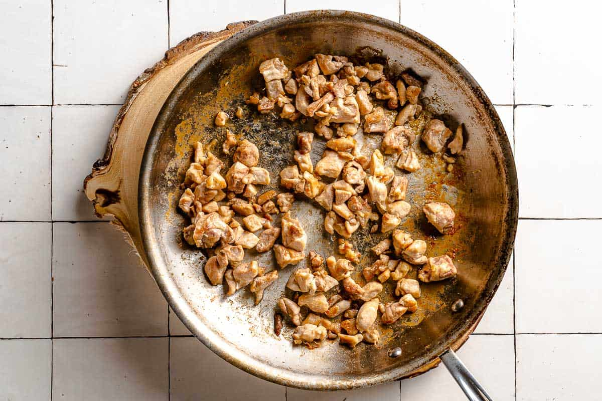 chicken pieces browning in pan