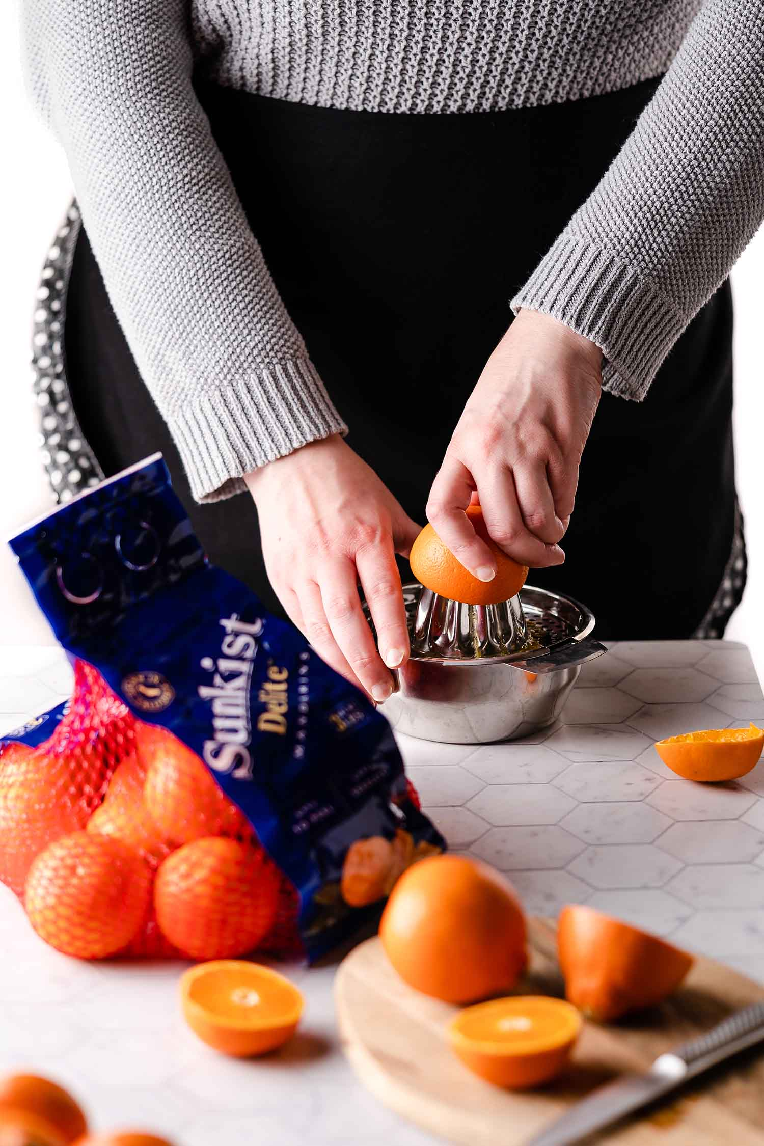 juicing oranges with oranges on cutting board