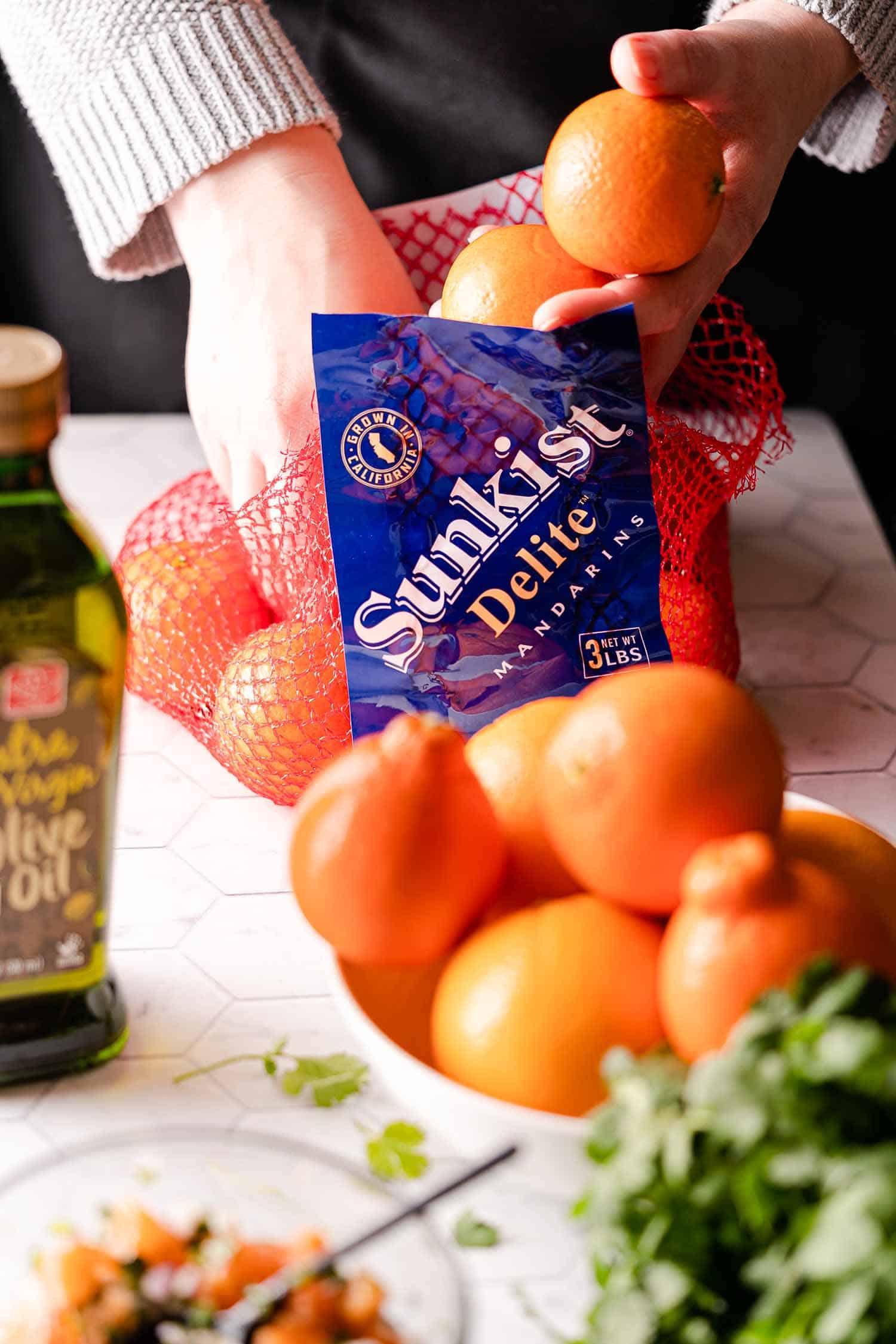 hands removing Mandarins from net bag