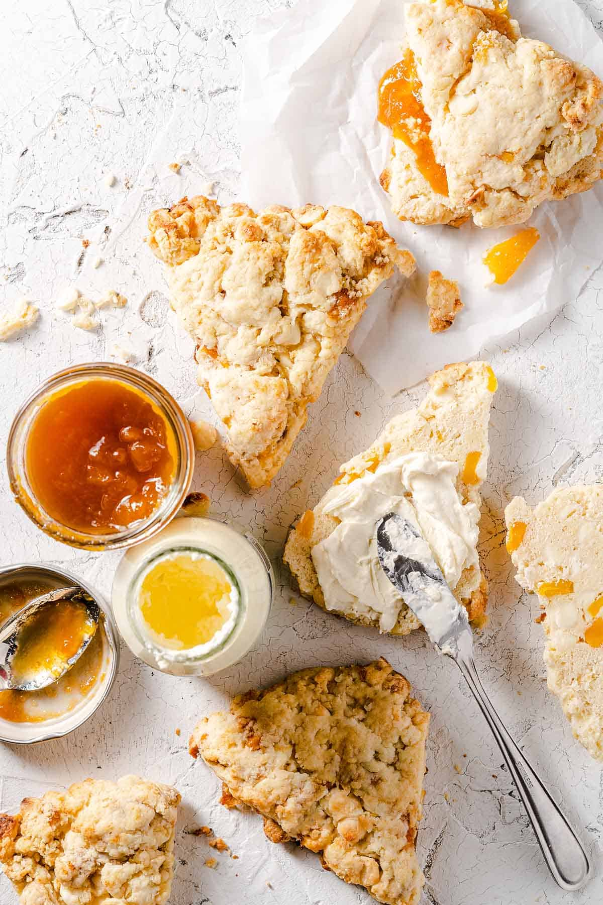 mango white chocolate scones with cream and jam being spread on top