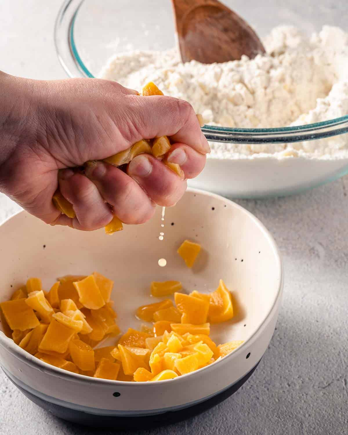 hand squeezing moisture off of soaked mango pieces
