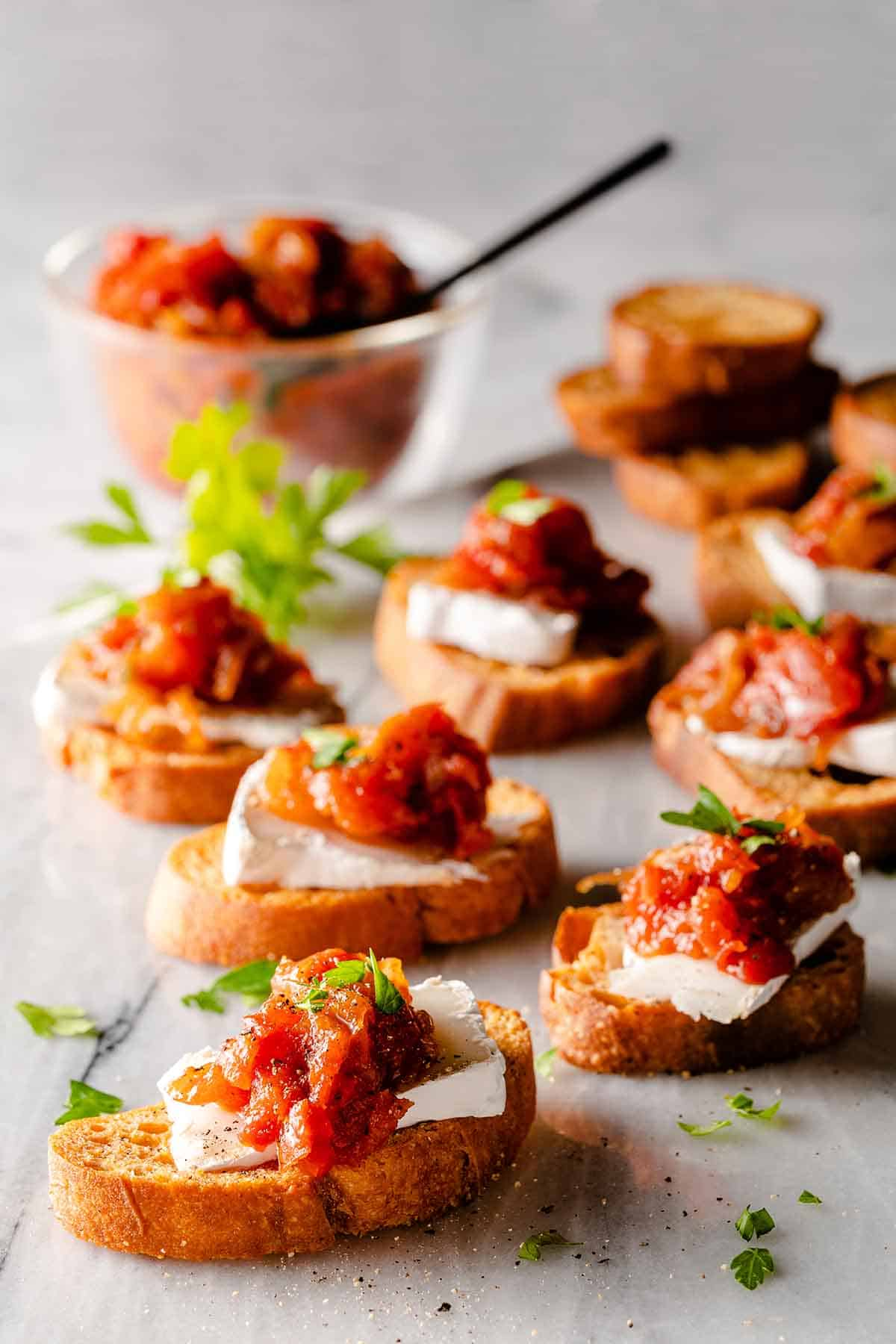onion tomato jam and cheese on crostini on marble board