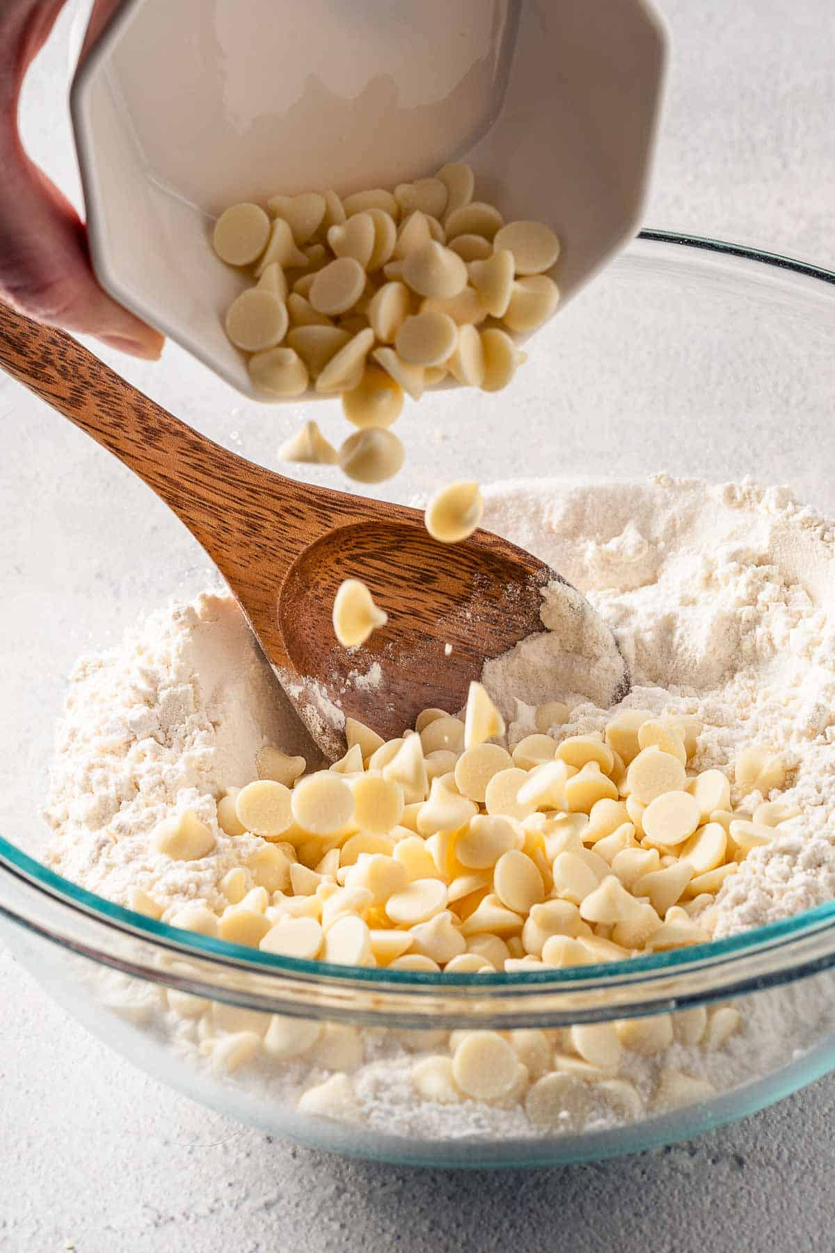 white chocolate chips being poured into dry scone ingredients