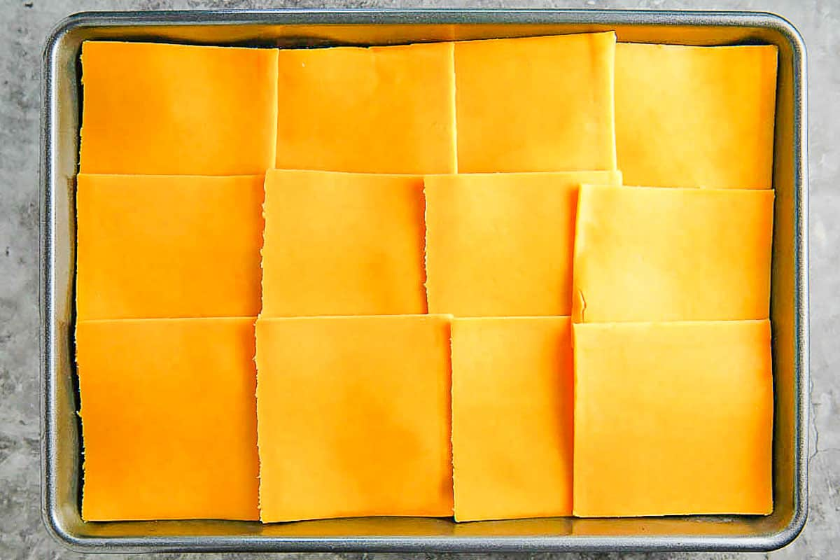 slices of cheese laid out on top of chili in baking pan