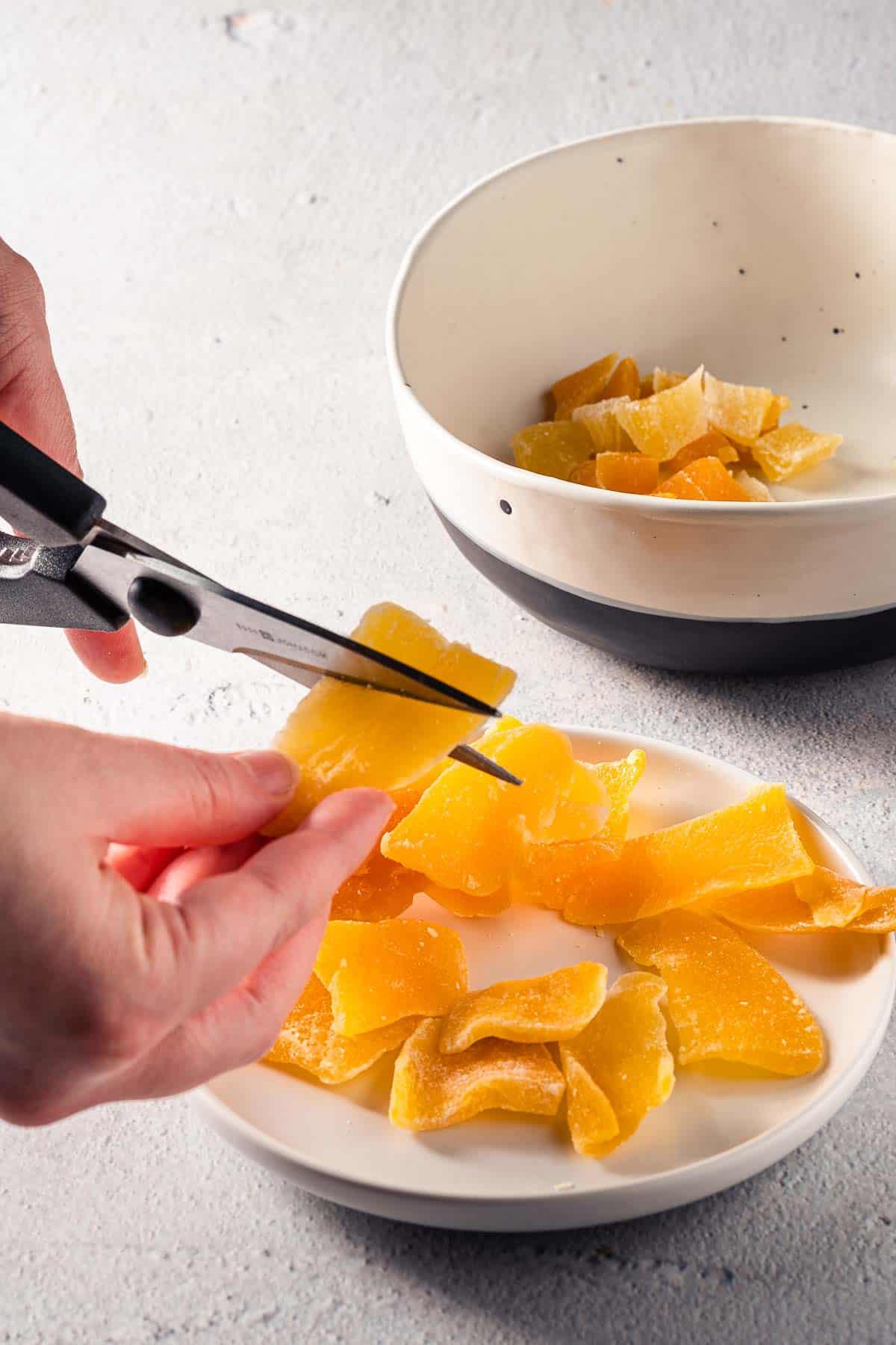 cutting dried mango with kitchen shears