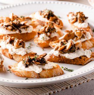 side view of ricotta mushroom crostini on white platter