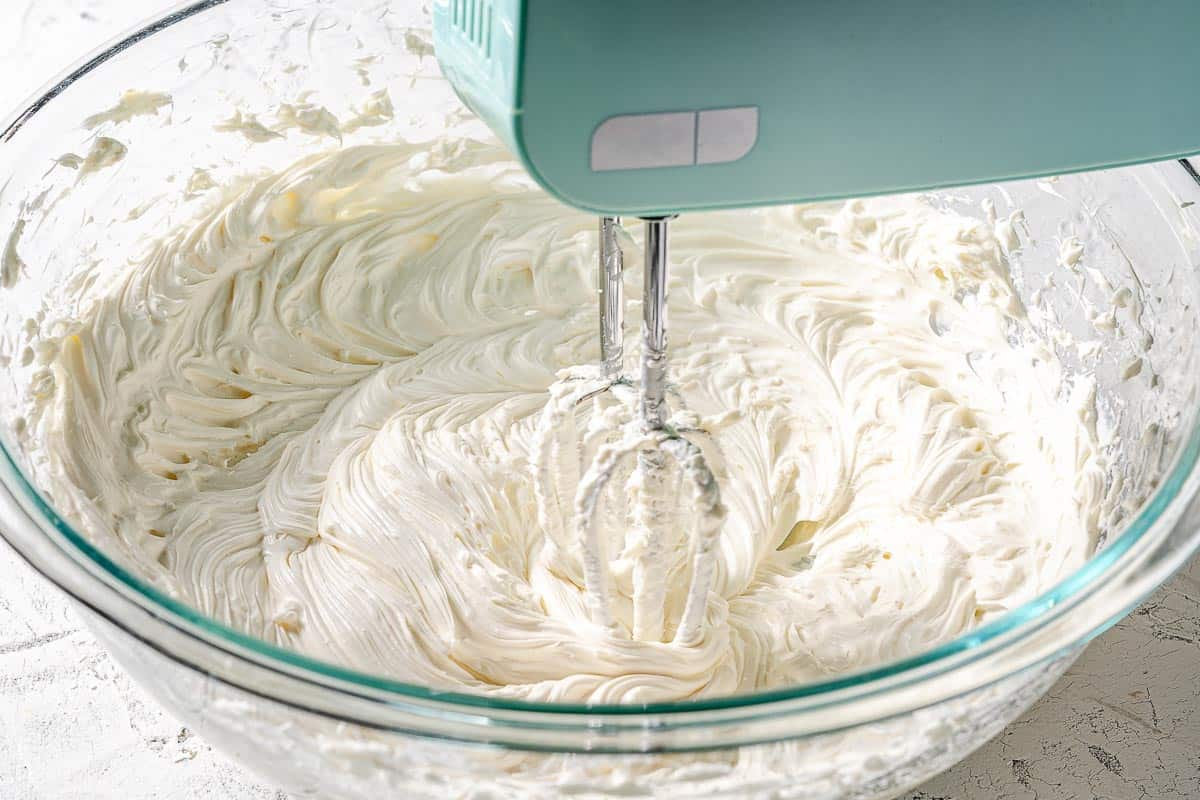 cream cheese vanilla and sour cream being mixed with hand beaters