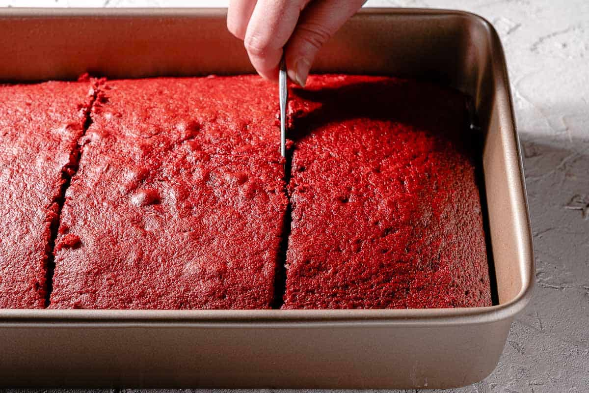 butter knife cutting red velvet cake into sections