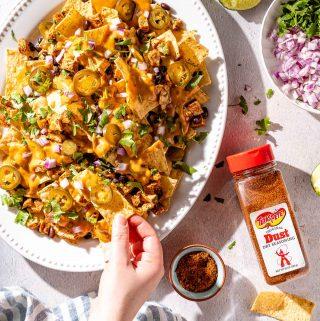 hand taking nacho from platter