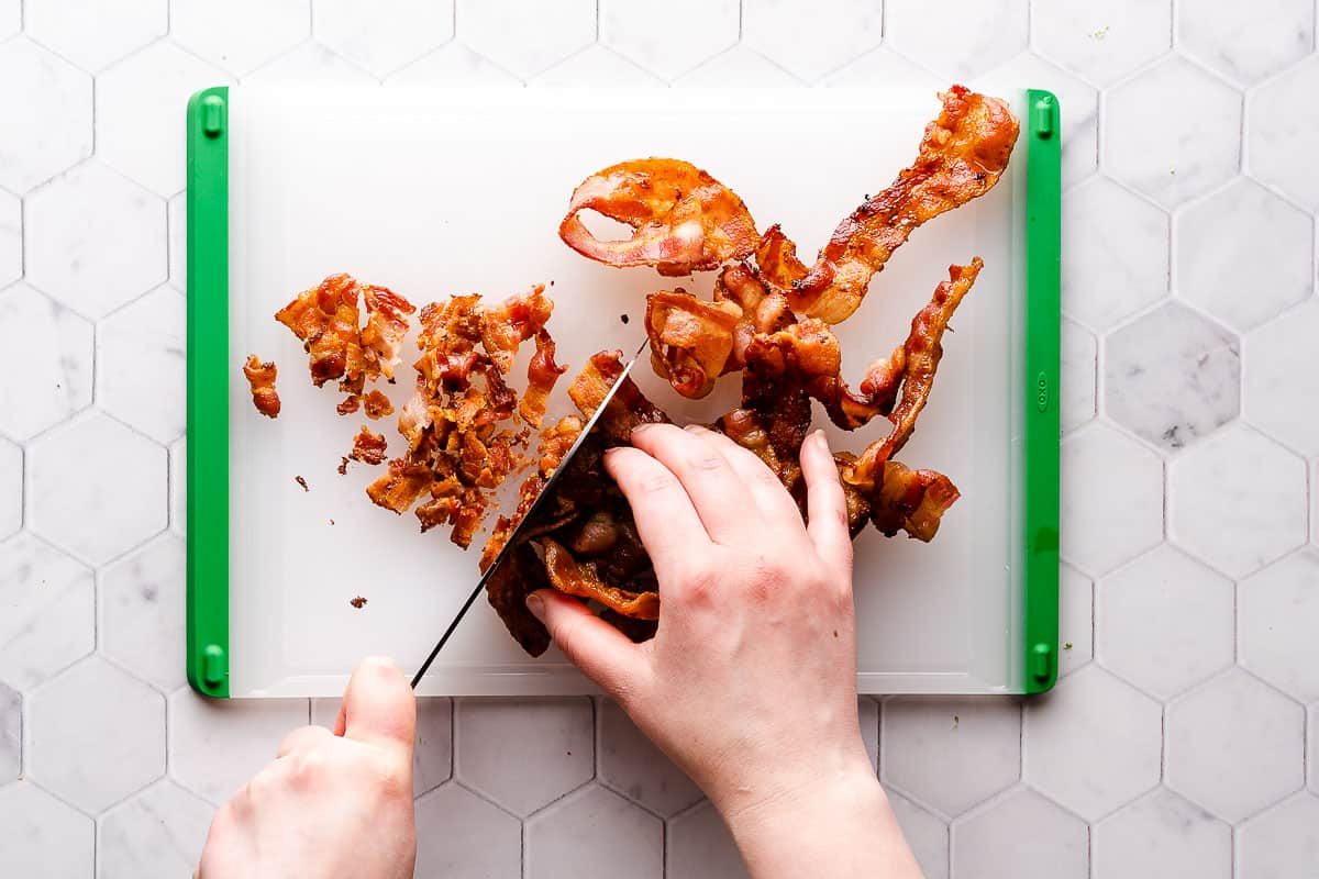 crispy bacon being chopped on cutting board