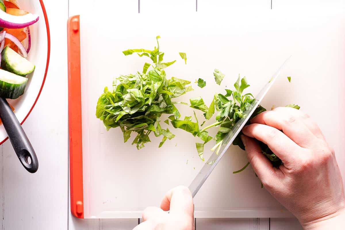 herbs being chopped on cutting board