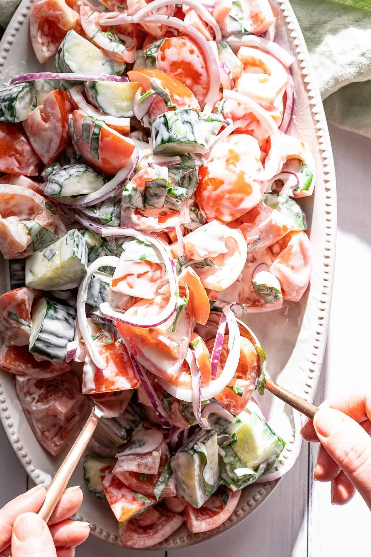 serving tomato salad from platter