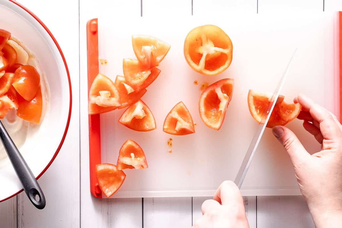 cutting tomatoes on cutting board with bowl on the side