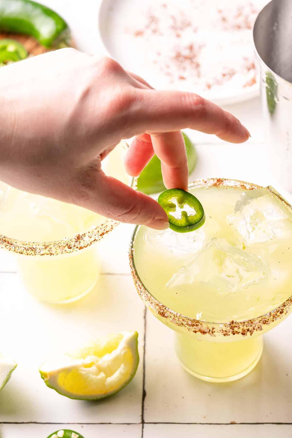 hand placing jalapeño garnish on spicy margarita