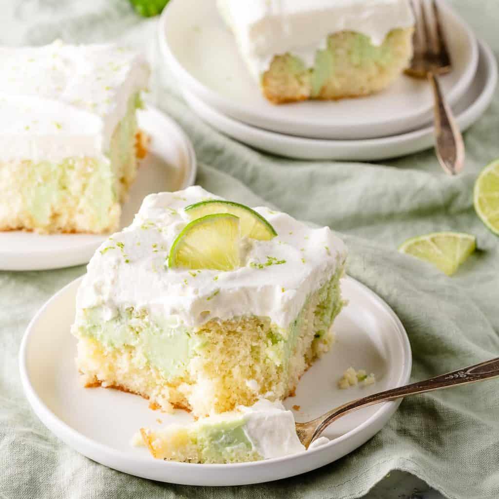 key lime poke cake on 3 plates with limes on the side