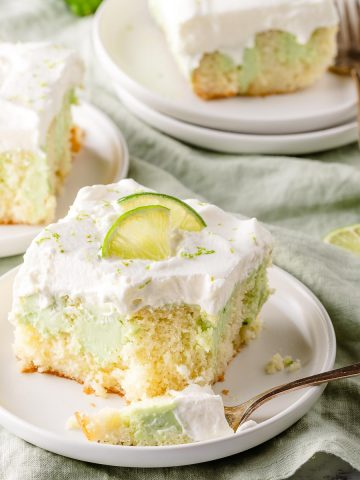key lime poke cake on 3 plates with limes on the side