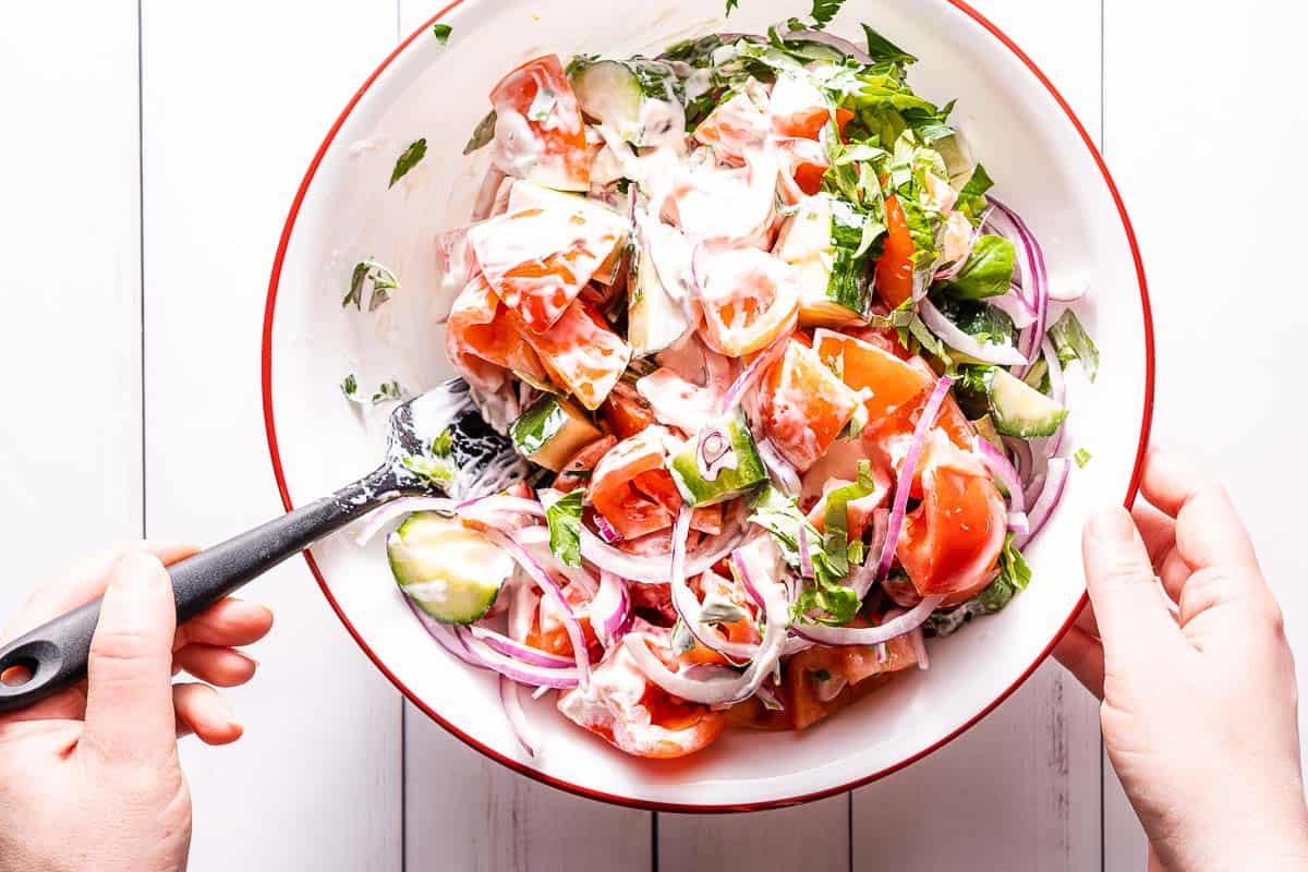 creamy tomato cucumber salad being mixed in large bowl