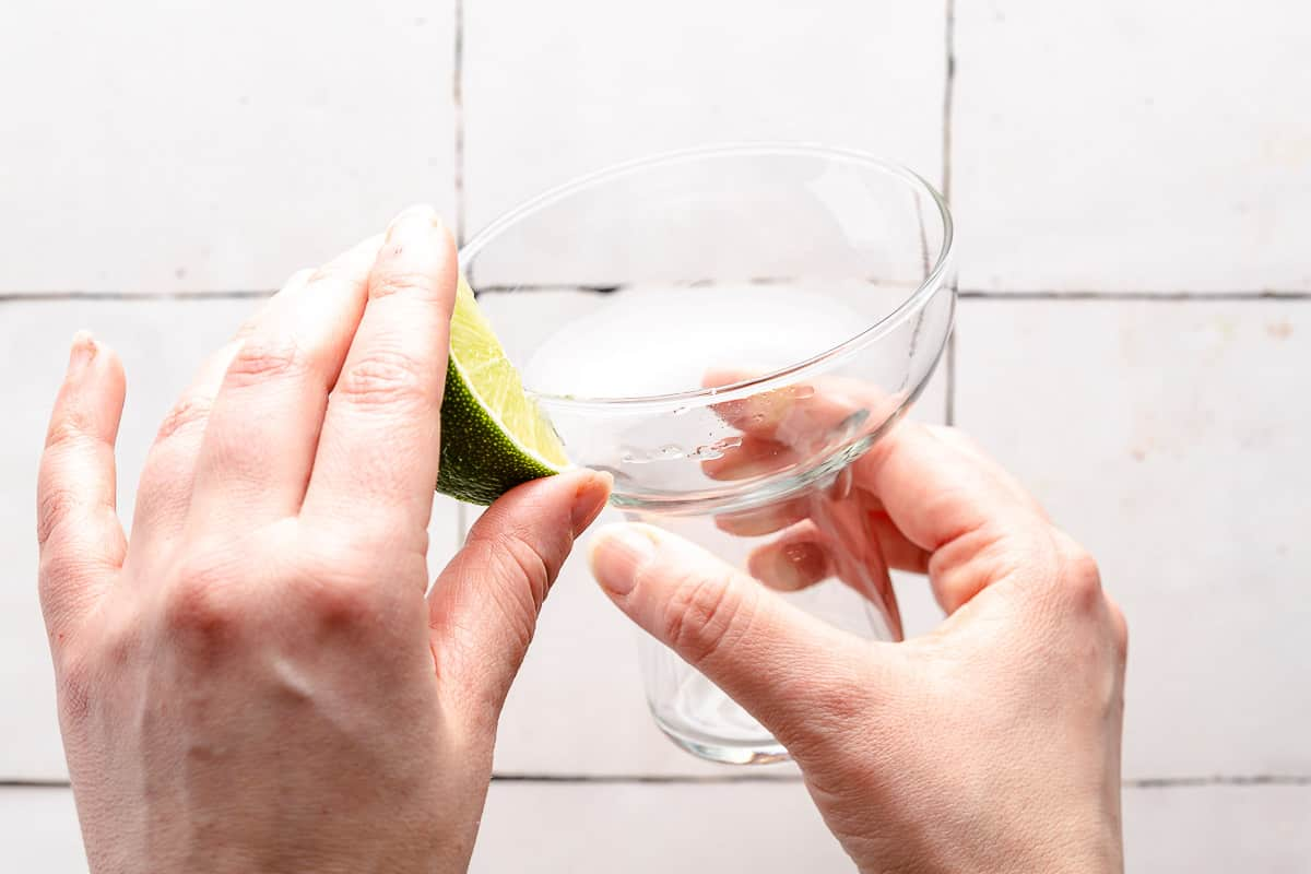 wedge of lime being rubbed on rim of glass