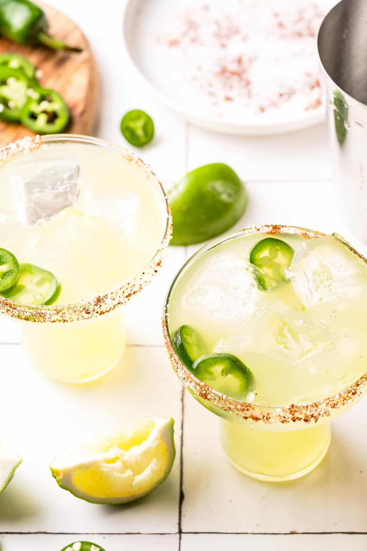 spicy margaritas in 2 glasses with jalapeño and salt in the background