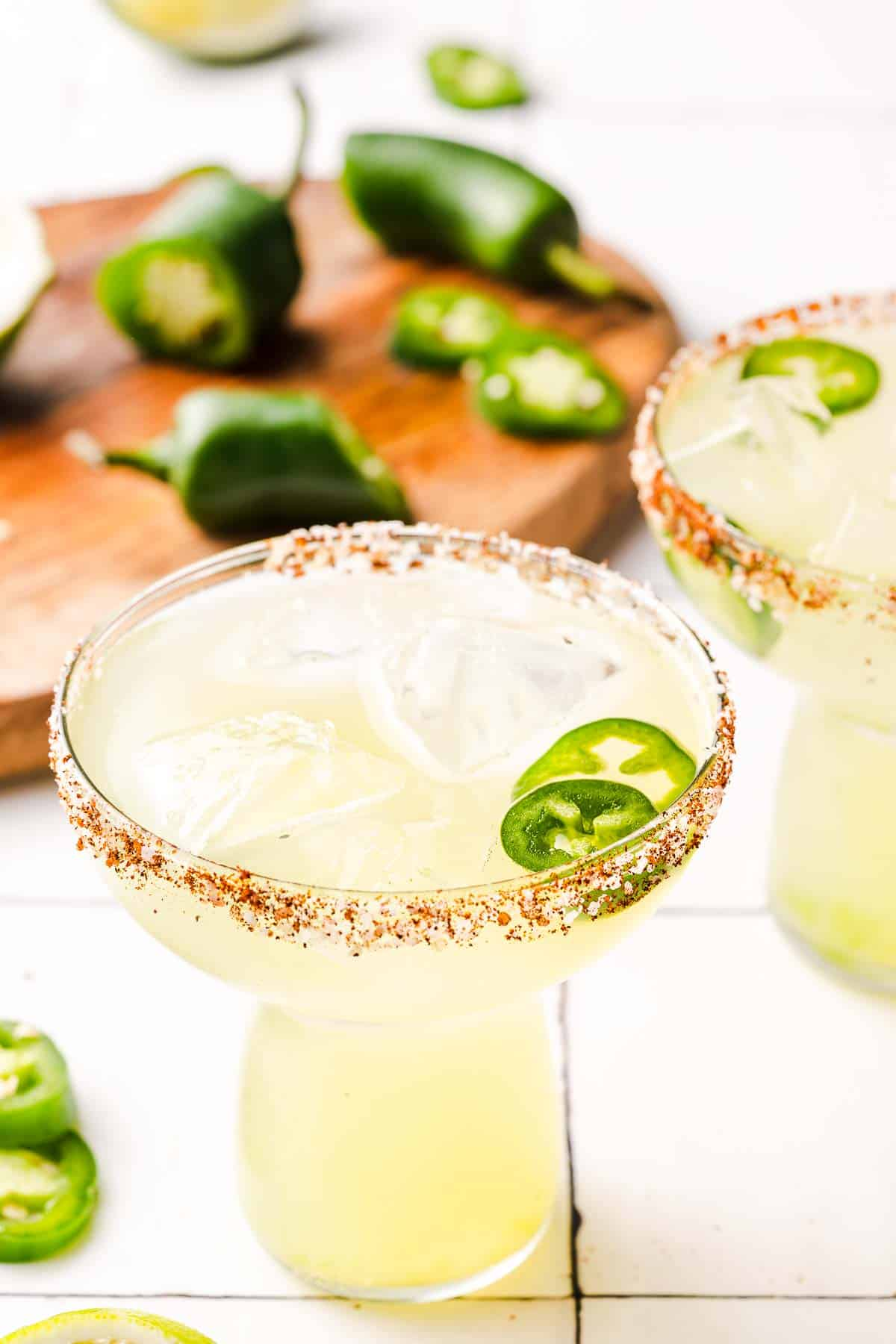 spicy margaritas with jalapeños in the background