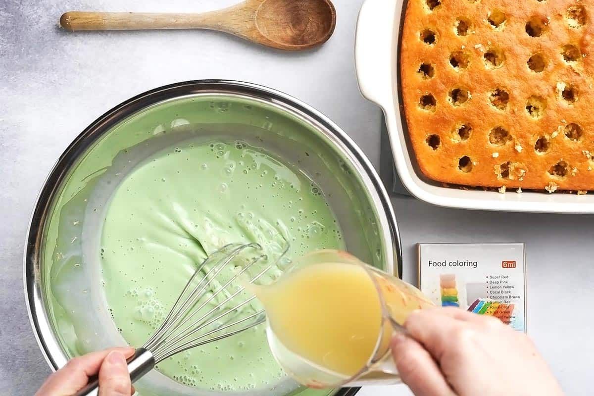 whisking Key lime juice into filling for poke cake with cake in the background