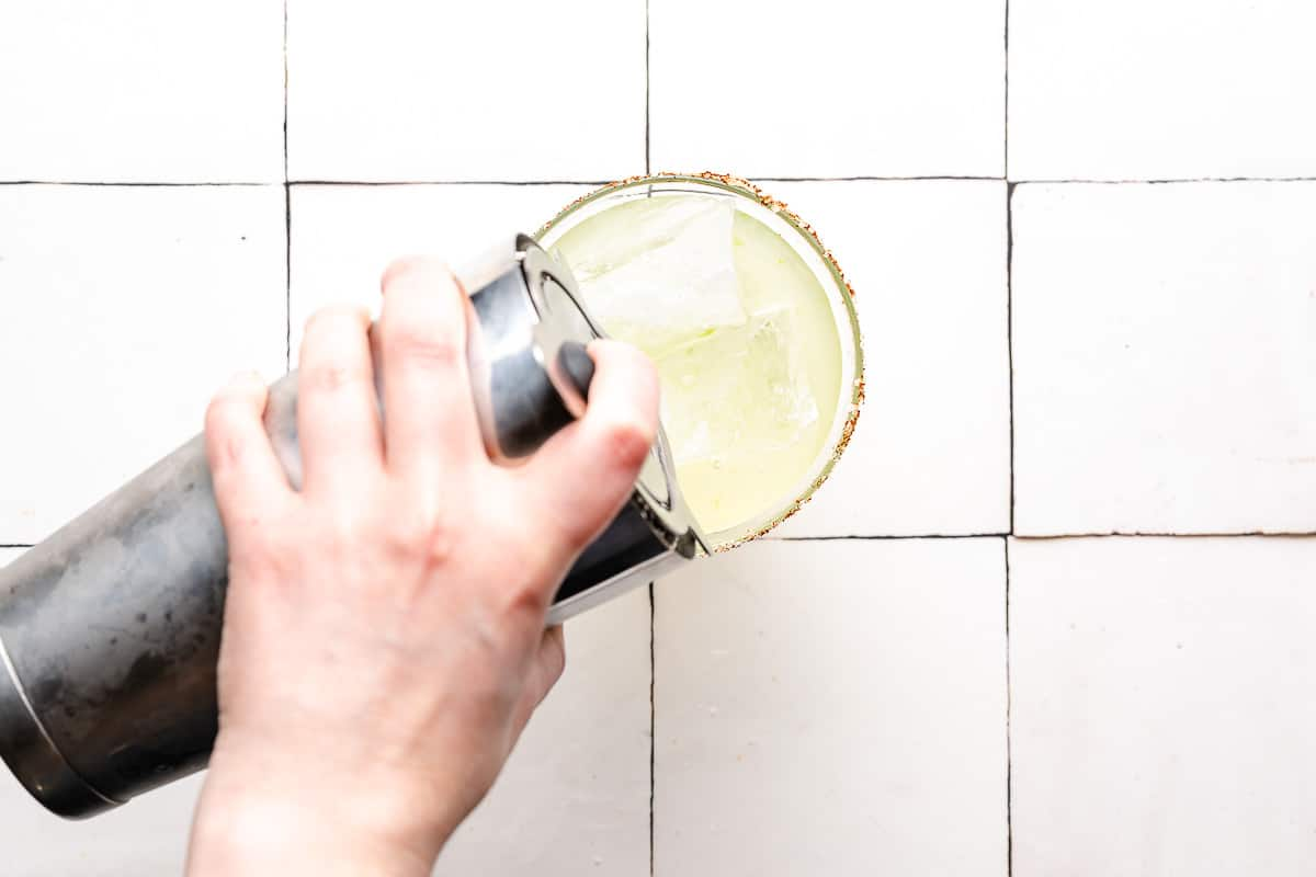 pouring margarita from cocktail shaker into glass