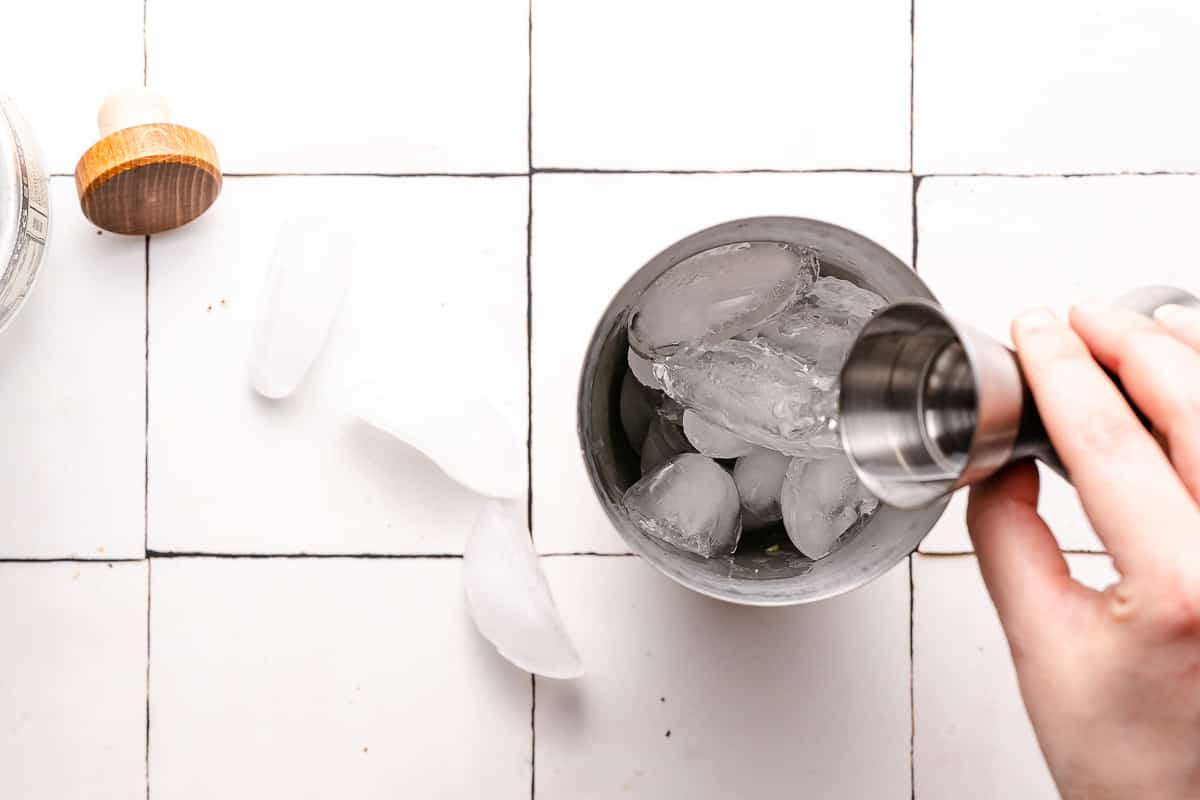 tequila being poured in a cocktail shaker filled with ice