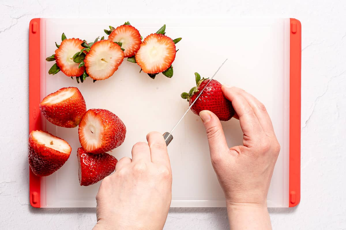 cutting tops off of strawberries on cutting board
